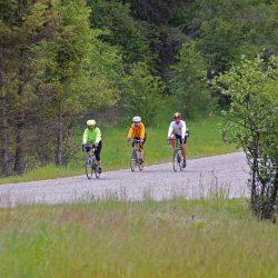 Three bike riders bike along a road in Aspen, Colorado