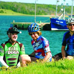 Cyclists pose for photo in front of water