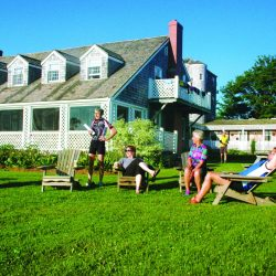 Bike tour guests relax in front of an inn