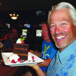 A man smiles holding a piece of chocolate cake