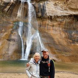 people posing in front of a waterfall