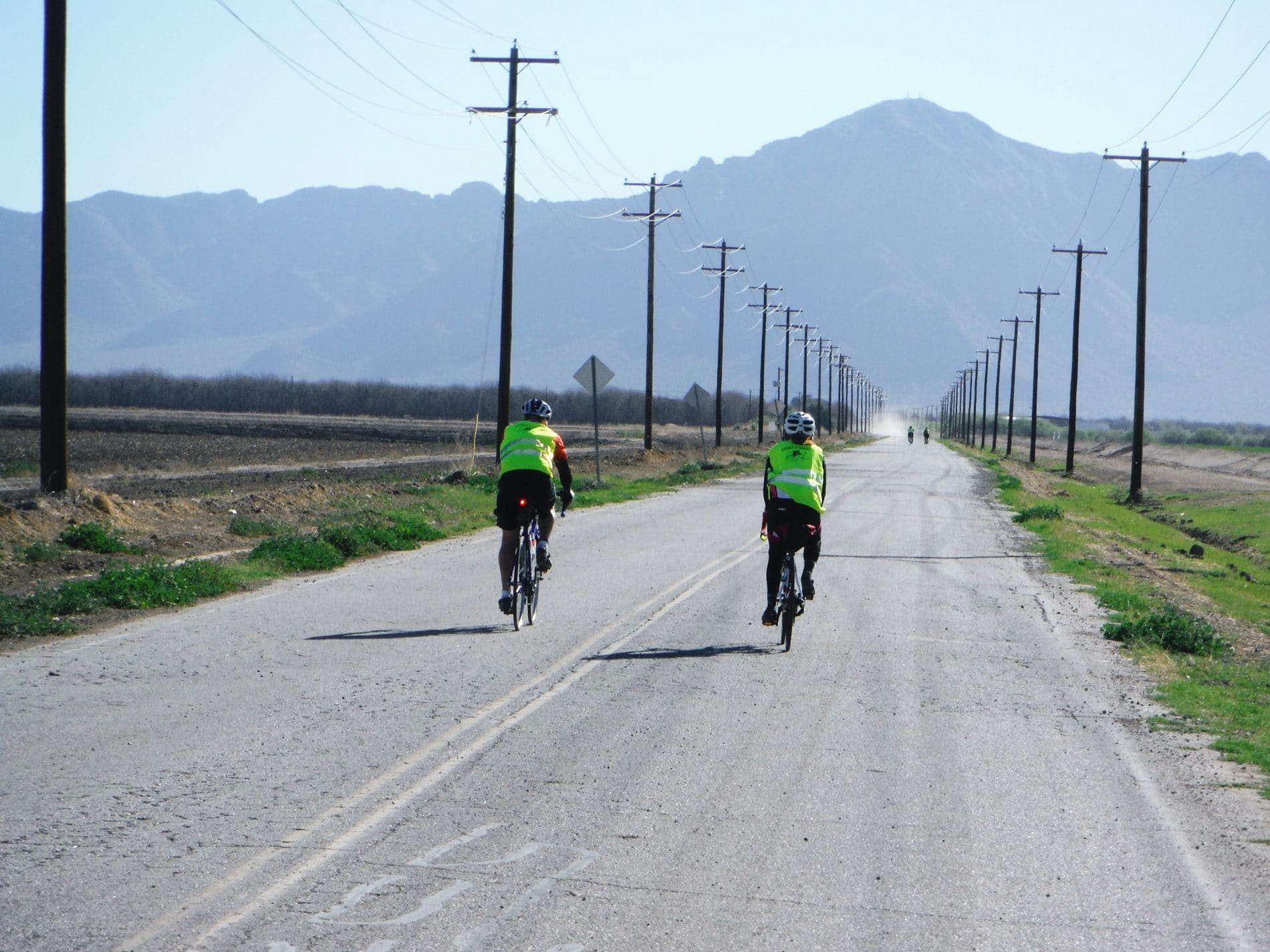 two bikers on a long road