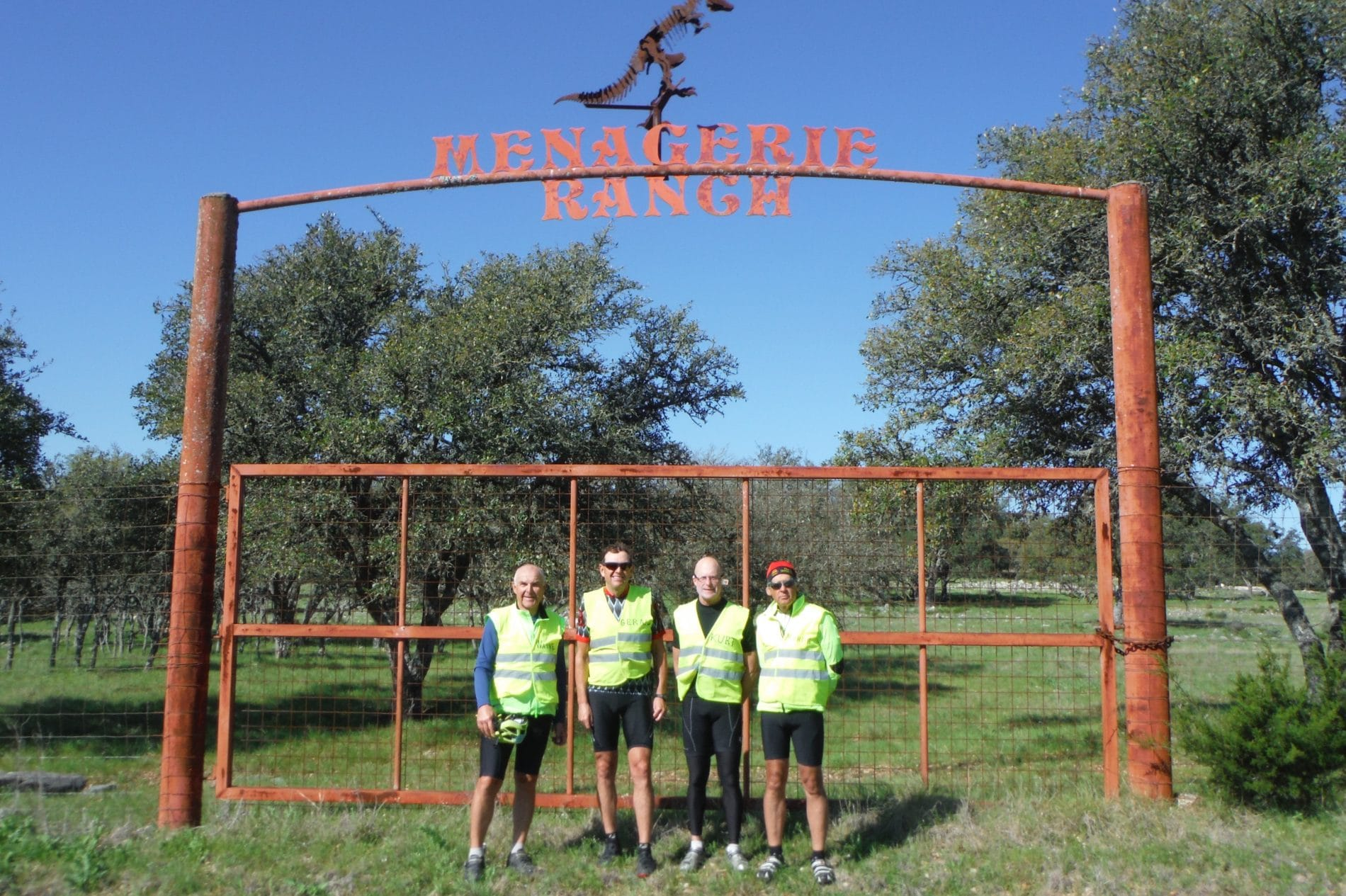 group of 4 people in front of a ranch sign