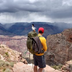 hiker overlooking grand canyon