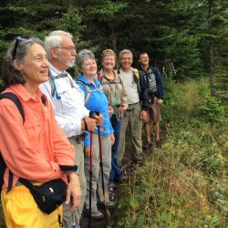 A group of hikers pose in a line in Isle Royale National Park
