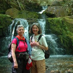 two hikers in front of a waterfall