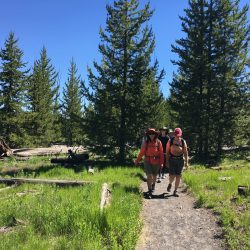Two hikers pose on a trail in Yellowstone National Park