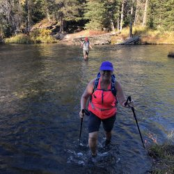 hiker in a river in Yellowstone