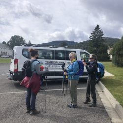 group of hikers in front of a white van