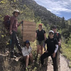 Group of happy hikers next to a trail sign