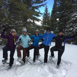 Snowshoers pose in the snow on a snowshoe tour