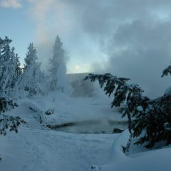 Yellowstone National Park with snow and a steaming pool